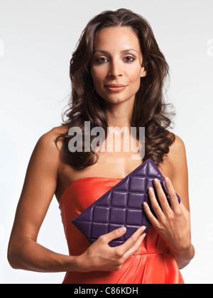 Schöne Frau trägt ein rotes Kleid und eine Kupplung in ihren Händen hält. Isoliert auf weißem Hintergrund. - Stockfoto