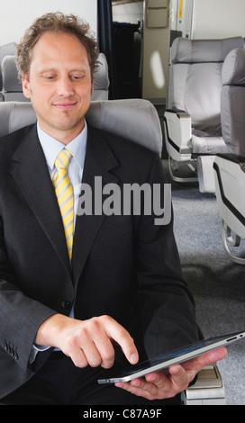 Deutschland, Bayern, München, Geschäftsmann mit Tablet PC in Business Klasse Flugzeug-Kabine, lächelnd - Stockfoto