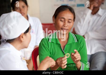 Frauen erhalten eine Kondom-Demonstration in einer Klinik der reproduktiven Gesundheit in Kampong Cham, Kambodscha, - Stockfoto