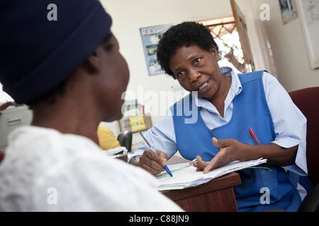 Eine Krankenschwester berät sich mit einem positiven HIV-Patienten in einer AIDS Relief Klinik unterstützt von Catholic Relief Services in Kitwe, Sambia.