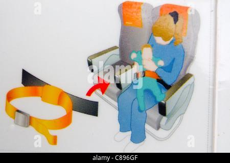 Nahaufnahme einer Airline Sicherheit Karte zeigt, wie man einen Kind Sicherheitsgurt benutzen - Stockfoto