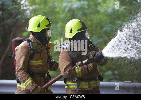 Feuerwehrleute mit einem Schlauch tragen von Atemschutz, UK - Stockfoto