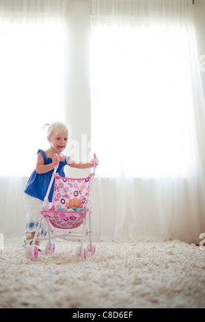 Kleinkind Mädchen schieben Spielzeug Kinderwagen mit Baby-Puppe