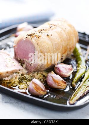 Braten-Sattel des Lammes gerollt mit Fromage Frais und Minze und gebratenem Knoblauch - Stockfoto