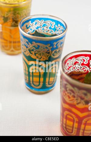 Kleine farbige Gläser Pfefferminztee auf weißem Hintergrund. - Stockfoto