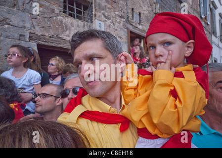 Ein Vater hält seinen kleinen Sohn, beide für das jährliche Festival der Corsa dei Ceri in Gubbio, Italien gekleidet - Stockfoto
