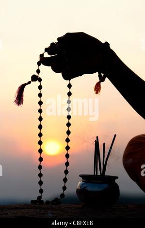 Mans Hand mit indischen Rudraksha / Japa Mala Gebet Perlen und Weihrauch. Silhouette
