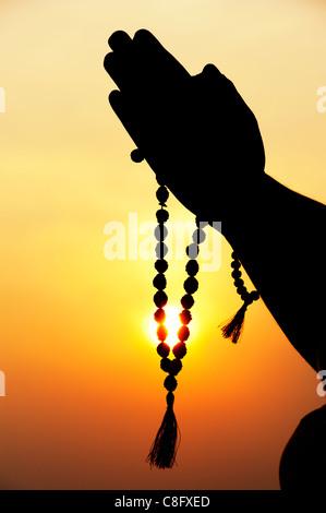 Mans Gebet Hände halten indischen Rudraksha / Japa Mala Gebetskette. Silhouette Stockfoto