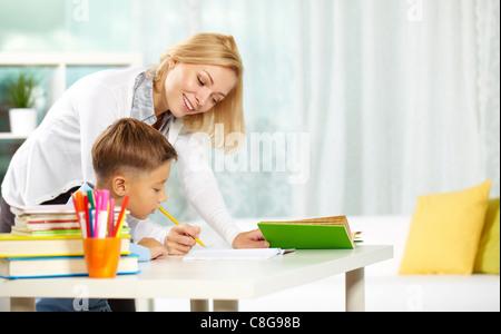 Porträt von intelligenten Tutor mit Bleistift, die Korrektur von Fehlern in Schülers notebook - Stockfoto