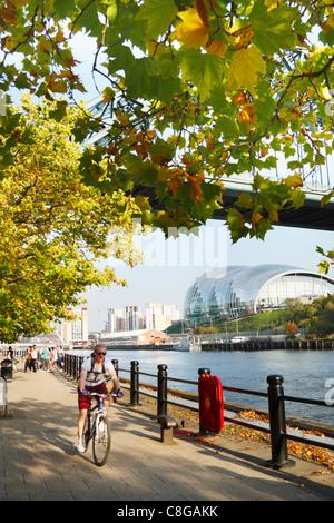 Radfahrer auf Kai unter dem Tyne Bridge in Newcastle Upon Tyne, England, Vereinigtes Königreich - Stockfoto
