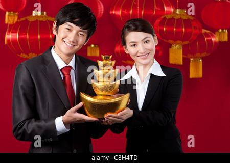 Geschäftsleute, die mit chinesischen Gold Yuanbao - Stockfoto