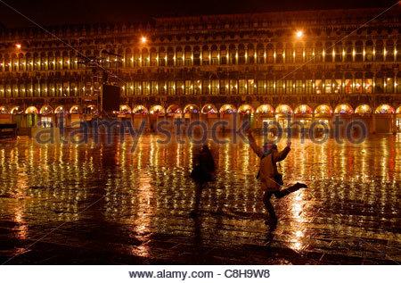 Eine Frau posiert in Piazza San Marco an einem regnerischen Abend. - Stockfoto