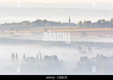 Blick auf Glastonbury vom Gipfel des Glastonbury Tor an einem nebligen Morgen kurz nach Sonnenaufgang - Stockfoto