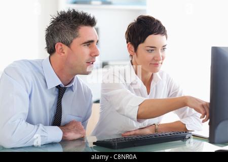 Geschäftsfrau, zeigen etwas auf einem Bildschirm zu ihrer Kollegin - Stockfoto