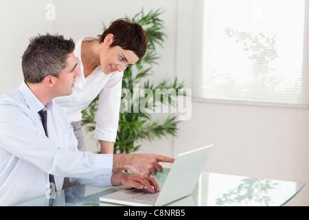 Mann zeigte sich etwas zu seinem Kollegen auf einem laptop - Stockfoto