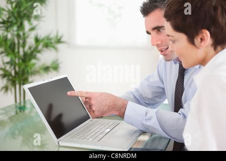 Manager zeigt auf etwas mit seinem Sekretär auf einem notebook - Stockfoto