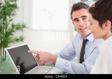 Manager zeigt auf etwas mit seinem Sekretär auf einem laptop - Stockfoto