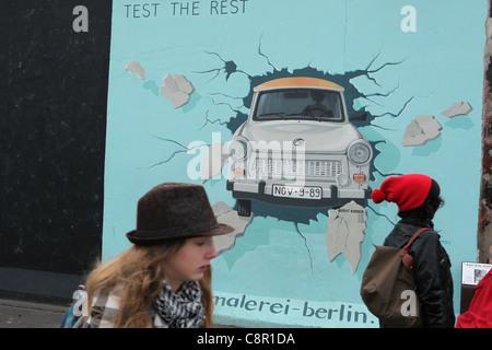Trabant, bricht durch die Wand abgebildet auf der Berliner Mauer im East Side Gallery in Berlin, Deutschland. - Stockfoto