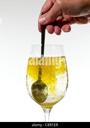 Olivenöl in einer großen Weinkelch bilden goldene Perlen in der Flüssigkeit gerührt wird - Stockfoto
