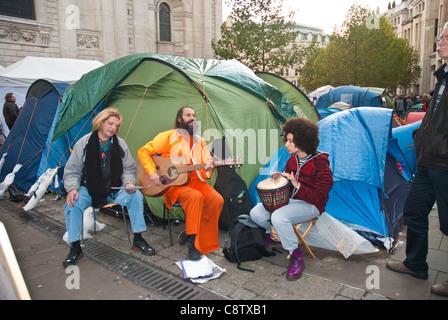 Occupy London, St Pauls, drei Menschen singen mit Gitarre / Schlagzeug vor Zelten. - Stockfoto