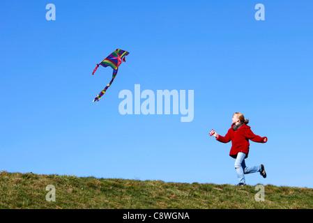 Mädchen, 10 Jahre alt, läuft mit einem Drachen fliegen lassen. - Stockfoto