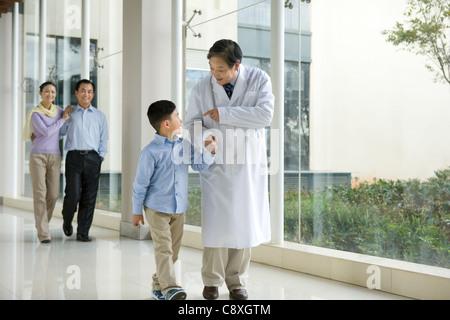 Junge Familie geht in einem Krankenhausflur mit einem Arzt - Stockfoto