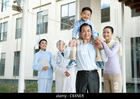 Junge Familie steht mit einem Arzt und einer Krankenschwester in einem Krankenhausflur - Stockfoto