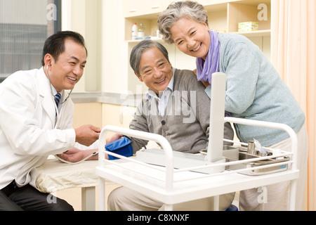 Ältere Mann mit seinen Blutdruck getestet von einem Arzt - Stockfoto