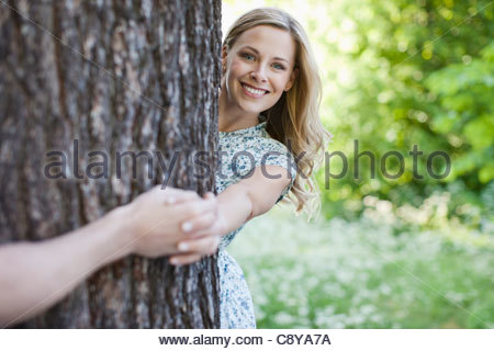 Paar halten Hände um Baum - Stockfoto