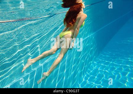 Junge Frau, die unter Wasser schwimmen im Schwimmbad - Stockfoto