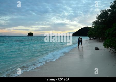 Romantisches Paar küssen am Strand, Wayag Insel, Raja Ampat Inseln, West-Papua, Indonesien in der Coral Triangle - Stockfoto