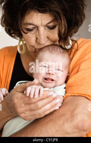 Großmutter wiegte schreiendes Kind - Stockfoto