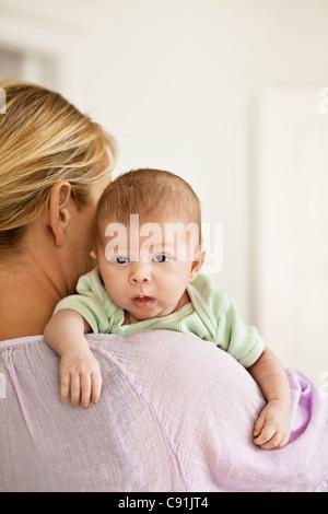 Mutter wiegt Kind auf Schulter - Stockfoto