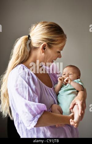 Mutter wiegt Baby - Stockfoto