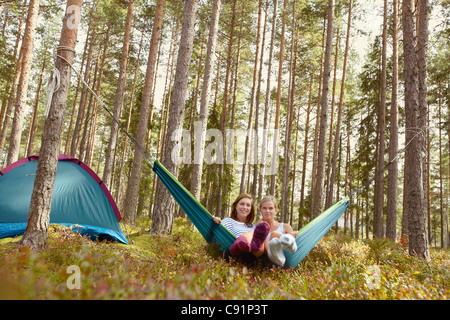 Frauen, die zum Entspannen in der Hängematte auf Campingplatz - Stockfoto