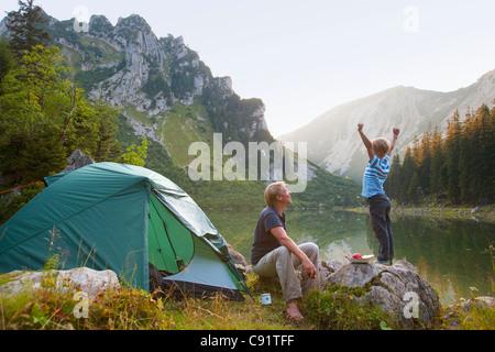 Vater und Sohn entspannend auf Campingplatz - Stockfoto