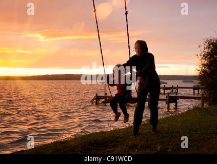 Mutter drängt Tochter auf Schaukel - Stockfoto
