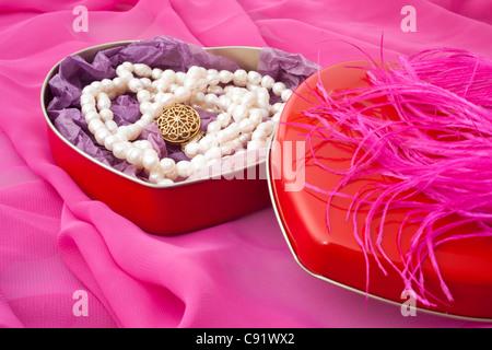 Perlen in einer herzförmigen Schachtel auf einem rosa Hintergrund - Stockfoto
