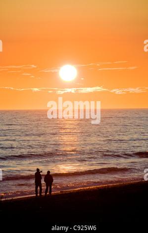Ein paar Spaziergänge Homer Spit Strand bei Sonnenuntergang entlang Kachemak Bay, Kenai-Halbinsel, Yunan Alaska, - Stockfoto