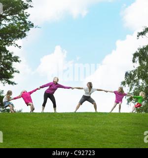 Mädchen spielen Tauziehen im Feld - Stockfoto