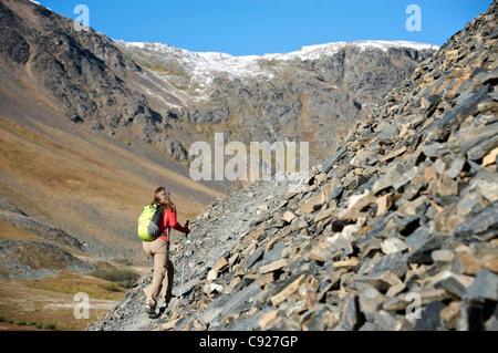 Wandern auf dem Crow Pass Trail entlang einer steilen felsigen Frau neigen, Chugach Mountains, Yunan Alaska, Herbst - Stockfoto