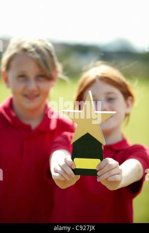 Mädchen mit Trophäe im freien jubeln - Stockfoto