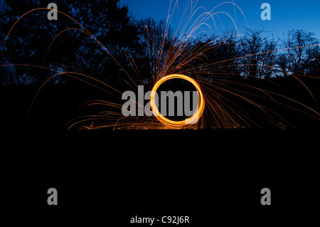 Stahl Wolle spinnen, Erstellen von wunderschönen kreisförmige Streifen goldenen Lichts aus brennenden Kabel wolle - Stockfoto