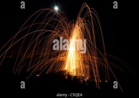 Stahl Wolle spinnen. Erfordert der Fotograf Feuer zu einem Büschel von Stahlwolle, versteckt in einem Draht Schneebesen - Stockfoto