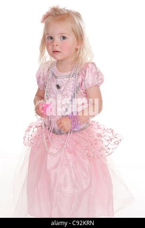kleines Mädchen in rosa Fee Kleid vorläufig Blick in die Kamera vor weißem Hintergrund - Stockfoto