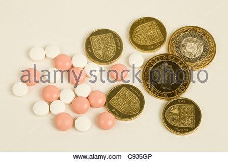 Rosa und weiße Pillen mit ein- und zwei-Pfund-Münzen - Stockfoto