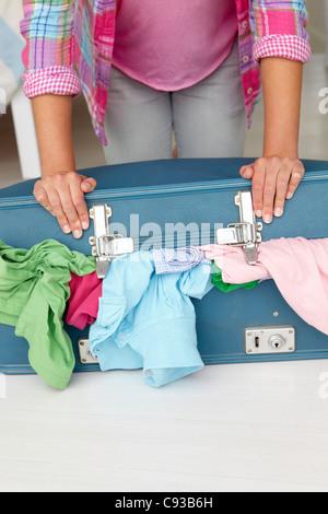 Teenager-Mädchen kämpfen, um Koffer zu schließen - Stockfoto