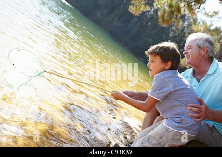 Großvater und Enkel mit Fischernetz - Stockfoto