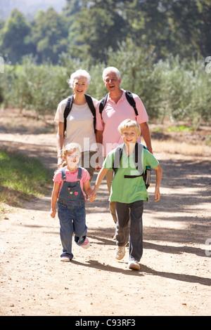 Älteres Paar und Enkel auf Land zu Fuß - Stockfoto