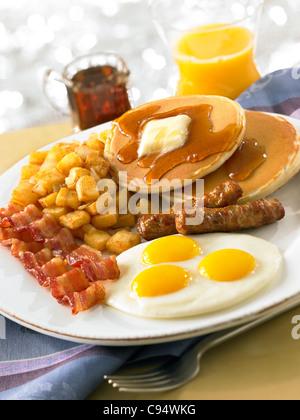 Pancake-Frühstück mit Eiern, Speck, Wurst, Kartoffeln und Orangensaft